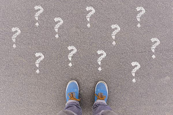 Person standing over question marks