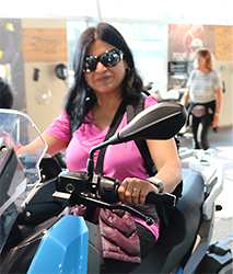 Shilpa, wearing sunglasses, on a blue BMW motorcycle